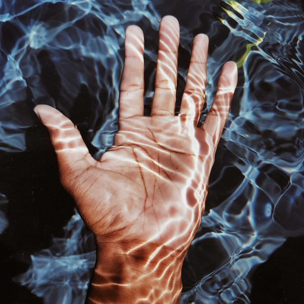 photo-of-person-s-hand-submerged-in-water-2499417